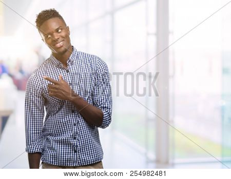 Young african american man wearing blue shirt cheerful with a smile of face pointing with hand and finger up to the side with happy and natural expression on face looking at the camera.