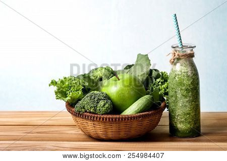 Close Up Green Apple With Mixed Green Vegetable And Green Juice In A Basket And Wooden Fork And Spoo