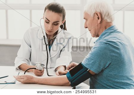 Young Female Doctor Examining Senior Patient. Young Woman Doctor Wearing White Coat Examining Senior