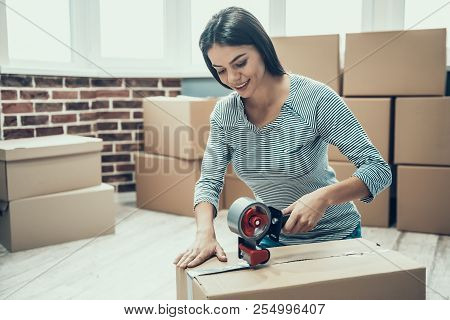 Young Smiling Woman Packing Cardboard Box At Home. Happy Beautiful Girl Preparing To Relocation By P