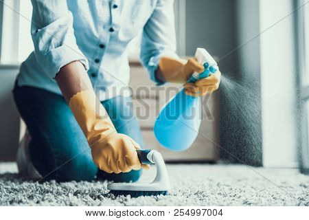 Young Beautiful Woman Cleaning Carpet With Brush. Closeup Of Girl Wearing Protective Gloves Cleaning