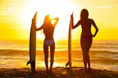 Saturated, stylised, rear view silhouettes of beautiful sexy young women surfer girls in bikinis with surfboards on a beach at sunset or sunrise poster