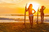 Saturated, stylised, rear view silhouette of two beautiful sexy young women surfer girls in bikini with surfboards on a beach at sunset or sunrise poster