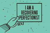 Text sign showing I Am A Recovering Perfectionist. Man hand holding paper communicating information dots turquoise background. poster