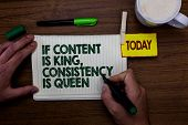 Word writing text If Content Is King, Consistency Is Queen. Business concept for Marketing strategies Persuasion Man holding marker notebook clothespin reminder wooden table cup coffee. poster