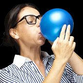portrait of middle aged woman blowing a balloon over black background poster