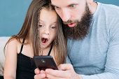 family leisure. shocked amazed and astonished dad and kid daughter reaction to smth they see on the phone. inappropriate advertisement or compromising photo on father's smartphone. poster