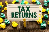 Text sign showing Tax Returns. Conceptual photo Tax payer financial information Tax Liability and Payment report Clothespin holding notebook paper crumpled papers several tries mistakes. poster