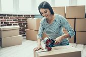 Young Smiling Woman Packing Cardboard Box at Home. Happy Beautiful Girl Preparing to Relocation by Packing Carton Boxes with Scotch Tape. Young Girl Moving to new Apartment poster