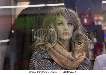 Female Mannequin With Long Blond Hair In A Checkered Coat, With A Scarf Shawl On The Neck