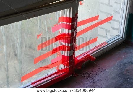 Red Duct Tape On A Window Pane. Two Windows Are Fastened With Duct Tape. A Pile Of Cigarette Ash On