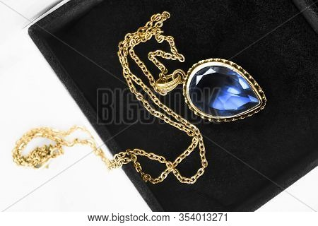 Gold Necklace With Large Blue Crystal Pendant In Jewel Box Closeup