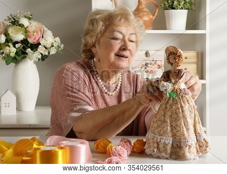 An Old Retired Woman Is Passionate About Creating Dolls  In Her Studio. Hand Made Art Crafts Theme
