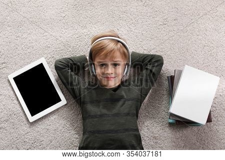 Cute Little Boy With Headphones And Tablet Listening To Audiobook On Floor Indoors, Flat Lay