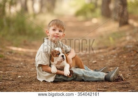 Beautiful Baby Boy With An English Bulldog Puppy, Hugging, Playing, Smiling, Looking At The Camera.
