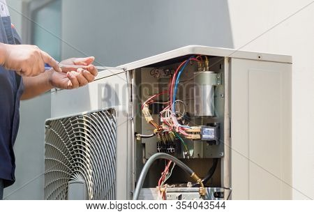 Male Technician Hands Using A Screwdriver Fixing Modern Air Conditioner, Repairing And Servicing, Ma