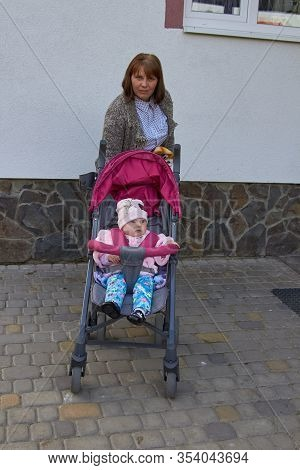 Mom With Her Daughter On A Walk With A Stroller, Mother With Her Daughter Goes For A Walk In A Strol