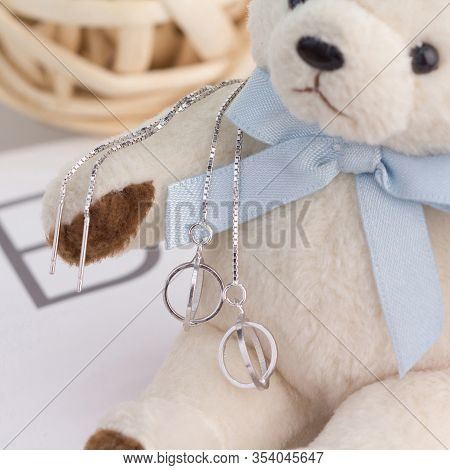 A Pair Of Beautiful 925 Sterling Silver Earrings Display On A Toy Bear