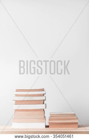 Stacks Of Books On A Wooden Shelf, On Neutral Background With Copy Space.