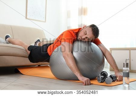 Lazy Young Man With Sport Equipment At Home