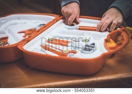 A Kid Is Going To Play With A Hammer, Tweezers, Stethoscope, Syringe And Other Toy Tools From A Toy