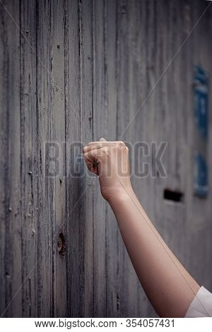 Hand Is Knocking On An Old Wooden Door, Anybody Home?