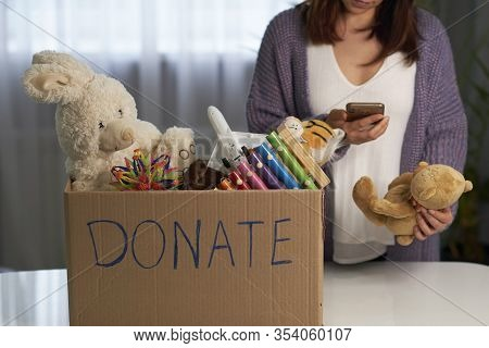Donation Box With Children Toys. Woman Collects Toys For Charity. A Woman Holds A Smartphone In Her