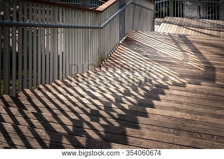 Staircase With A Shadow From The Railing. A Descending Staircase With Wooden Steps And Metal Railing