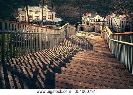 Staircase With A Shadow From The Railing. A Staircase Descending From The Mountain With Wooden Steps