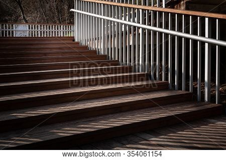 Staircase With A Shadow From The Railing. Go Back Down The Ladder With Wooden Steps And Metal Railin