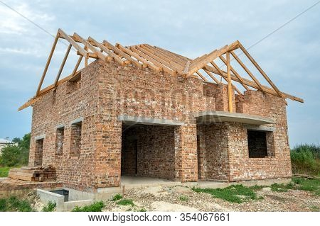 Building Site With Unfinished Brick House With Wooden Roofing Frame For Future Roof Under Constructi