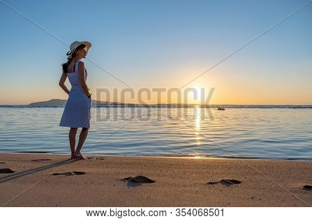 Young Woman In Straw Hat And A Dress Standing Alone On Empty Sand Beach At Sunset Sea Shore. Lonely