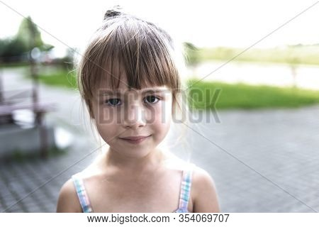 Close-up Portrait Of Pretty Young Little Blond Pale Unhappy Moody Friendless Child Girl Looking Sadl