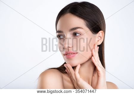 Portrait of beautiful young brunette woman with clean face. Beautiful face of young adult woman with clean fresh skin - isolated on white. Front portrait of woman with beauty face. Beauty concept