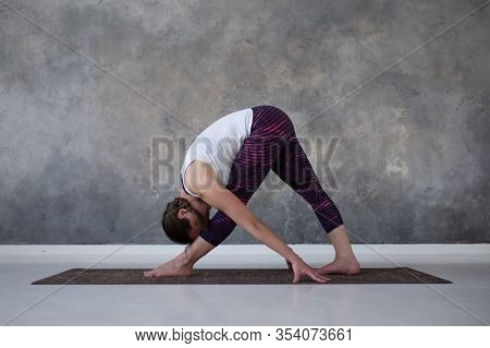 Woman Practicing Yoga, Standing In Parsvottanasana Pose On Mat, Pyramid Exercise