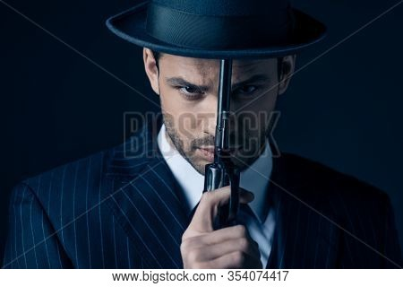 Portrait Of Gangster Holding Gun In Front Of Face On Dark Blue