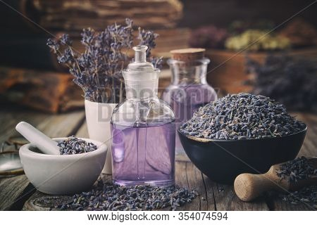 Bowl Of Dry Lavender Flowers, Mortars, Bottles Of Essential Lavender Oil Or Infused Water. Old Books