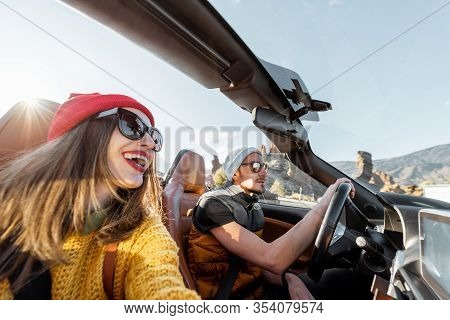 Selfie Portrait Of A Happy Couple While Driving Convertible Sports Car On The Desert Road During A S