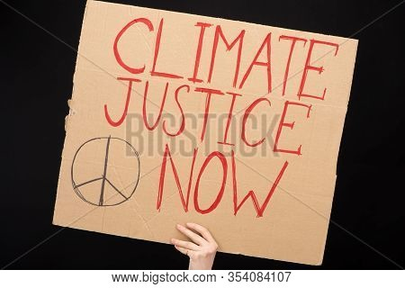 Partial View Of Woman Holding Placard With Climate Justice Now Lettering Isolated On Black, Global W