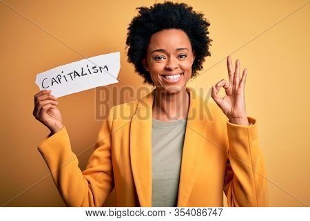 African American afro businesswoman with curly hair holding paper with capitalism message doing ok sign with fingers, excellent symbol