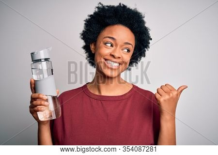 Young African American afro woman with curly hair drinking bottle of water for refreshment pointing and showing with thumb up to the side with happy face smiling