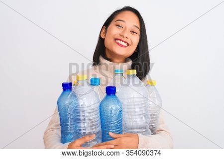 Young beautiful chinese woman recycling plastic bottles over isolated white background with a happy face standing and smiling with a confident smile showing teeth