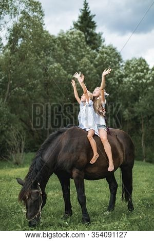 Two Funny Children Girls Sisters Friends Riding A Horse Together Through A Field. Girls Sitting On A