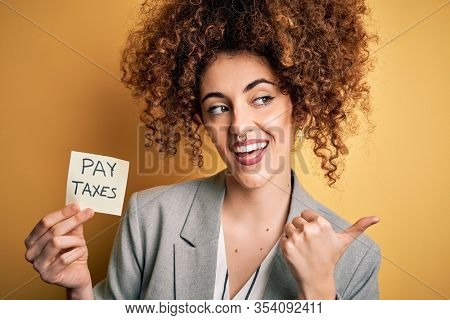 Young business woman with curly hair holding pay taxes to goverment reminder over yellow background pointing and showing with thumb up to the side with happy face smiling