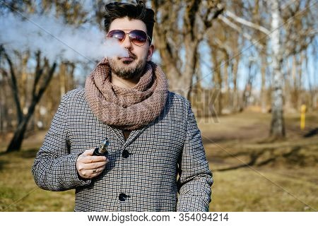 Confident Young Bearded Male In Sunglasses Vape Electronic Cigarette. A Young Handsome Bearded Hipst