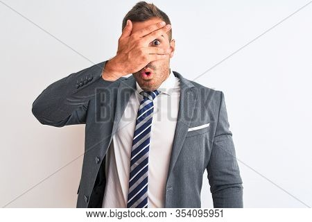 Young handsome business man wearing suit and tie over isolated background peeking in shock covering face and eyes with hand, looking through fingers with embarrassed expression.
