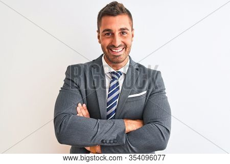 Young handsome business man wearing suit and tie over isolated background happy face smiling with crossed arms looking at the camera. Positive person.