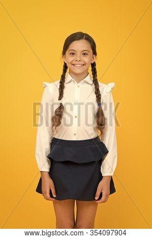 Smart Cutie. Cute Little Girl Smiling On Yellow Background. Happy Small Girl Wearing School Uniform.