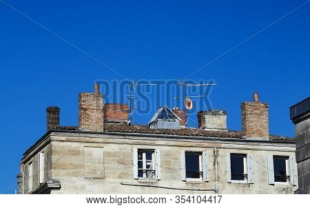 Ancient House With Different Kinds Of Chimneys And Antennas On The Top Of The Roofs Against Blue Sky