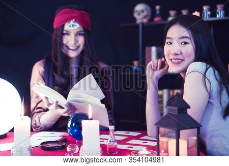 A Beautiful Asian Woman Is Performing A Ritual For Fortune Telling With The Fortune Teller, A Woman